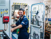 Marine engineer officer working in engine room royalty free stock image