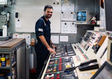 Marine engineer officer working in engine room. Marine engineer officer in engine control room ECR. Seamen`s work. He starts or stops main engine of ship stock image