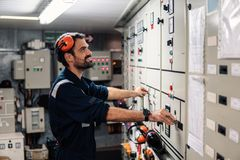 Marine engineer officer working in engine room. Marine engineer officer in engine control room ECR. Seamen`s work. He starts or stops main engine of ship royalty free stock photography