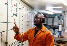 Marine engineer officer working in engine room. Marine engineer officer in engine control room ECR. Seamen`s work. He starts or stops main engine of ship stock photography
