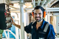 Marine engineer officer working in engine room stock photography