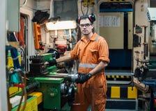 Marine engineer working in ship`s workshop in engine control room. ECR. Seamen`s work Royalty Free Stock Photos