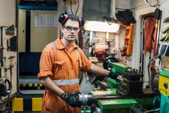 Marine engineer working in ship`s workshop in engine control room. ECR. Seamen`s work Royalty Free Stock Photography