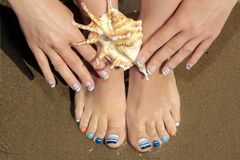 Marine French manicure and pedicure with blue and orange stripes on short nails on the coast stock photo