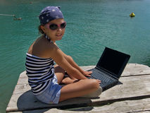 Marine girl with laptop on sea Royalty Free Stock Photo