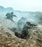 Marine Infantry Parachute Regiment. Squad of elite french paratroopers of 1st Marine Infantry Parachute Regiment RPIMA in action in enemy trenches filled with Royalty Free Stock Photo