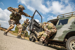 Marine Infantry Parachute Regiment. Squad of elite french paratroopers of 1st Marine Infantry Parachute Regiment RPIMA detaining terrorist in the car, low angle Royalty Free Stock Photos