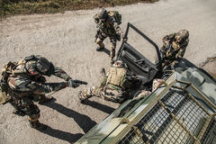 Marine Infantry Parachute Regiment. Squad of elite french paratroopers of 1st Marine Infantry Parachute Regiment RPIMA detaining terrorist in the car, top view Royalty Free Stock Photos