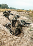 Marine Infantry Parachute Regiment. Squad of elite french paratroopers of 1st Marine Infantry Parachute Regiment RPIMA taking control enemy trenches, securing Royalty Free Stock Photos