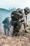 Marine Infantry Parachute Regiment. Two french paratroopers of 1st Marine Infantry Parachute Regiment RPIMA, in action jumping out of enemy trench filled with Stock Image