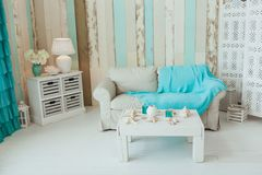 Marine Interior. White sofa and table, seashells, turquoise decor. Marine Interior. White sofa and rustic table, seashells, turquoise decor Royalty Free Stock Photo