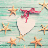 Marine items ( sea stars)  and decorative heart on  turquoise wo Royalty Free Stock Images