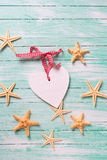 Marine items ( sea stars)  and decorative heart on  turquoise wo Stock Image
