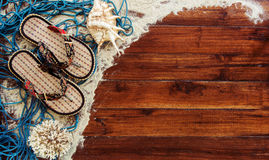 Marine items on wooden background. Sea objects - seashells, corals on wooden planks. Beach still life. Stock Photos