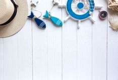 Marine items on wooden background. Sea objects: straw hat, swimsuit, fish, shells . flat lay, copy space stock photography