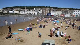 Marine lake beach Weston-super-Mare Somerset in summer sunshine with tourists and visitors stock video footage