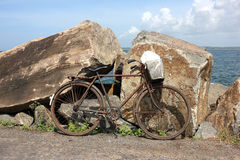 Marine landscape with bicycle. Photo image with large rock and  bicycle Stock Images