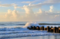 Ocean sunrise background. Marine landscape with splashes, scattering from the waves, beating about the remains of the old wooden pier in rising sun lights Stock Image