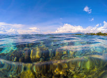Marine landscape with transparent water and sky. Transparent seawater with coral reef under water. Stock Photography