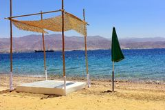 Marine a morning idyll. Beach on the Red Sea.early in the morning without people. in the foreground of a bamboo canopy and umbrella Royalty Free Stock Photo