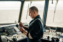 Marine navigational officer or chief mate on navigation watch. On ship or vessel. He fills up checklist. Ship routine paperwork stock image