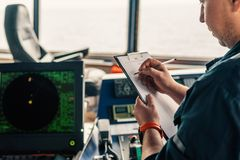 Marine navigational officer or chief mate on navigation watch. On ship or vessel. He fills up checklist. Ship routine paperwork stock photo