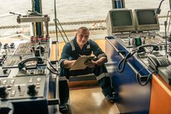 Marine navigational officer or chief mate on navigation watch. On ship or vessel. He fills up checklist. Ship routine paperwork royalty free stock photos