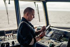Marine navigational officer or chief mate on navigation watch. On ship or vessel. He fills up checklist. Ship routine paperwork stock photography