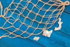 Marine Network och skal på blåa bräden Arkivfoto