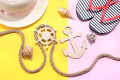 Marine paraphernalia and beach accessories. Wooden steering wheel and an anchor with a rope on a bright pink and yellow background. Top view stock photo