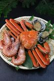Marine products helping of various kinds of dishes. I served an abalone, a deep red snow crab, red prawns to a colander Royalty Free Stock Photo