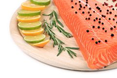 Marine raw fish fillets decorated. On a wooden table Royalty Free Stock Image