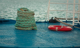 Marine rope and lifebuoy. Red lifebuoy and thick rope are lying on the ship deck. Summer on the Black Sea Stock Images