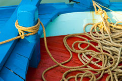 Marine rope tied around the boat's pole with lots of spare lengt Stock Photography