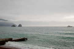 Marine scenery with far away cliffs and a yacht Stock Images