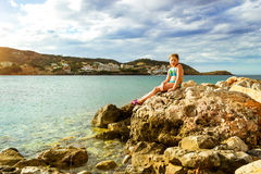 Marine spit on beach Livadi in resort Bali, Crete. Cute teenage girl posing on the background of breakwater of huge rocks going out to sea. Marine spit on beach Royalty Free Stock Photography