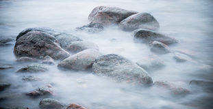 Marine stones washed by a wave. Close up Royalty Free Stock Photography