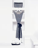 Marine style fashion. Women's clothing in white interior. Royalty Free Stock Photos