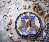 Marine style table setting with sea shells, fishnet and rope. Top view Royalty Free Stock Image