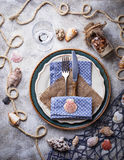 Marine style table setting with sea shells, fishnet and rope. Top view Stock Photography