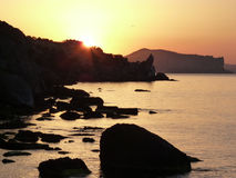 Marine sunrise. Sunrise. Sunbeams. Morning sea. Black silhouette of rocks. Marine stones. Crimea. The new World. Black sea. Beautiful sea-piece. Orange sky Stock Photo