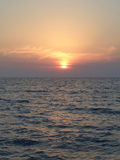 Marine sunset, sun in the haze of mauve clouds. Sea and sky at sunset Stock Photography