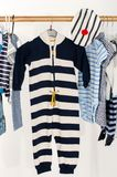 Dressing closet with baby striped clothes arranged on hangers. royalty free stock photos
