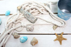 Marine theme. On wooden boards lying bottle with sand , seashells , starfish , a rope and a bucket Stock Photos