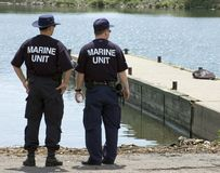 Marine Unit. Two policemen on the shore, watching carefully to their right Stock Image