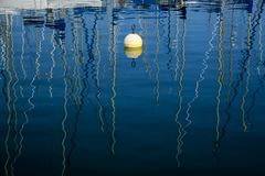 Marine water reflections. Beautiful reflections of the masts of yachts in a marina stock photos