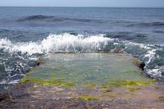 Marine wave breaks against off-shore stone Stock Photos