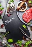 Marineert de bord kokende achtergrond met ruw lapje vlees, vleesvork, vers kruiden en, hoogste mening stock foto's