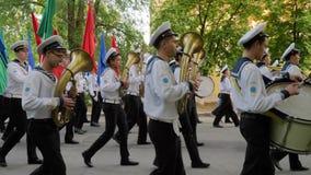 Marinehochschulband, die in eine Parade, Studenten im einheitlichen Spiel auf Musikinstrumenten und bunte Flaggen tragen marschie stock video