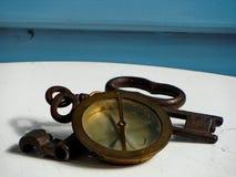 Marinekompaß und drei festes Eisen, verrostete Schlüssel auf weißem und blauem Hintergrund stockbild